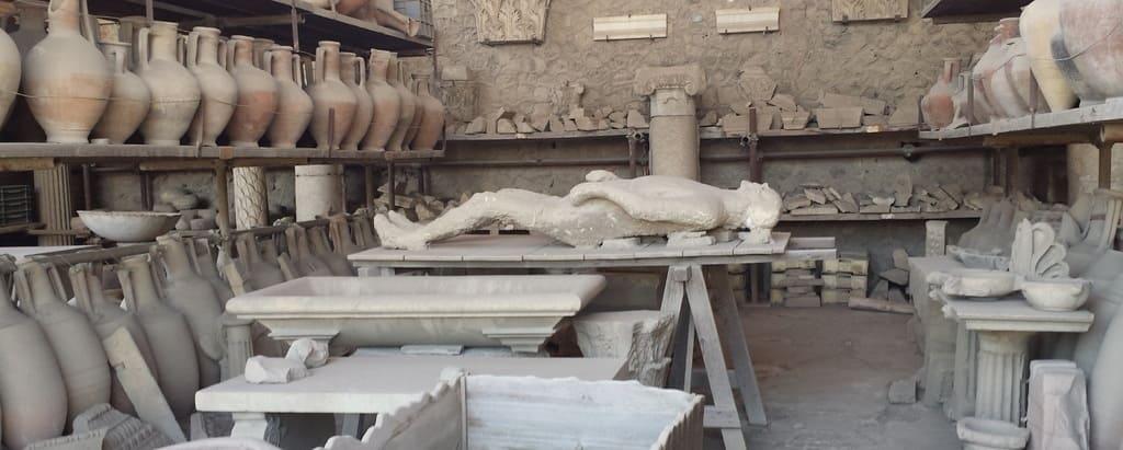Imagen de uno de los comercios mejor conservados de Pompeya junto con una de las esculturas de escayola para recrear los cuerpos encontrados.