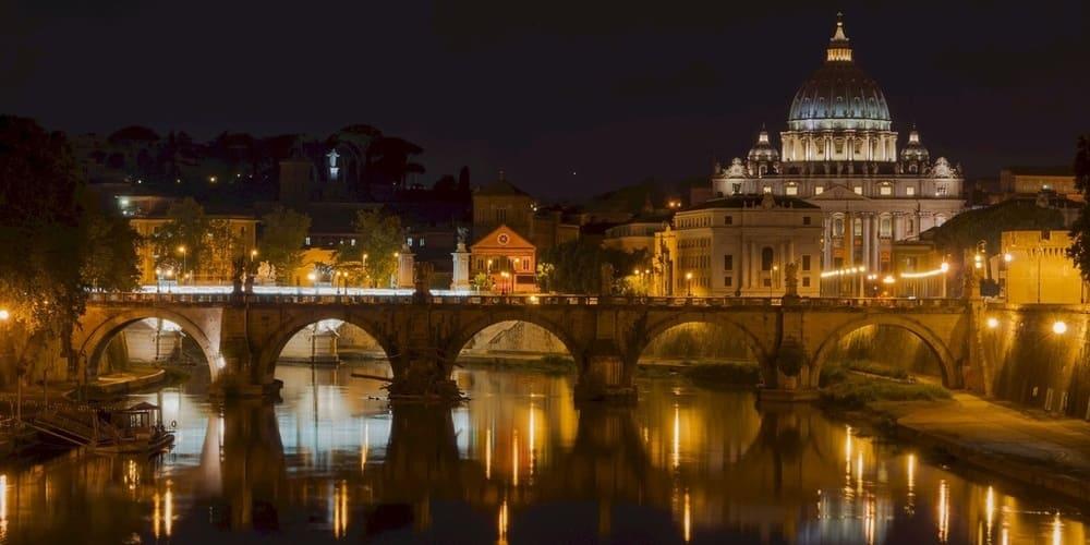 Viste del puente de Roma con la Basílica de San Pedro de fondo durante la noche.