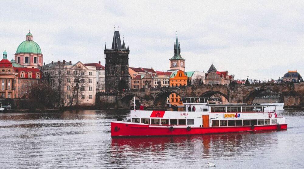 Barco por el río Moldava a su paso por el Puente de Carlos