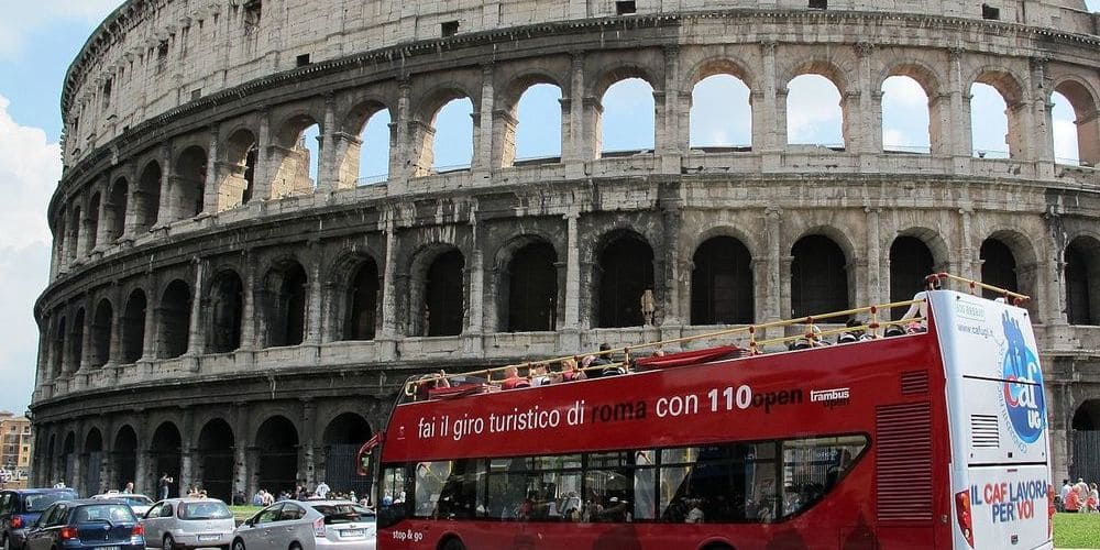 Bus turístico frente al Coliseo Romano.