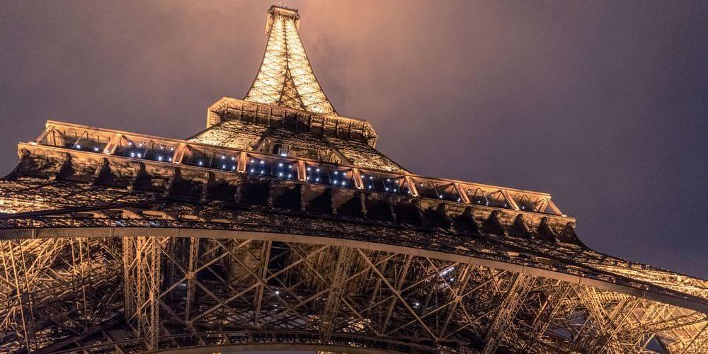 Vista inferior de la Torre Eiffel iluminada durante la noche.