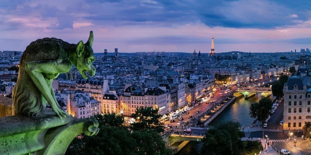 Fotografía aérea de París junto a una gárgola durante el amanecer acorde al tiempo, clima y temperatura en París en Marzo.