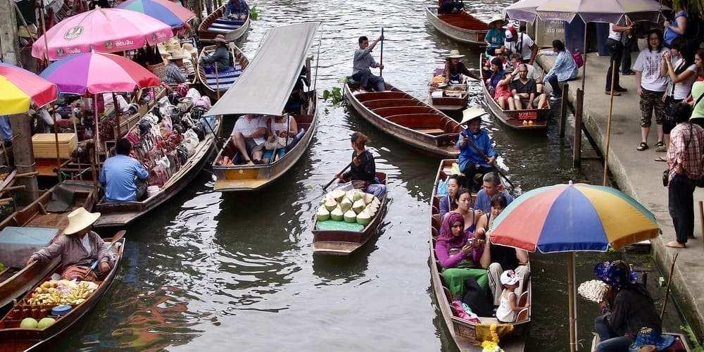 Turistas navegando por el mercado flotante de Tailandia.
