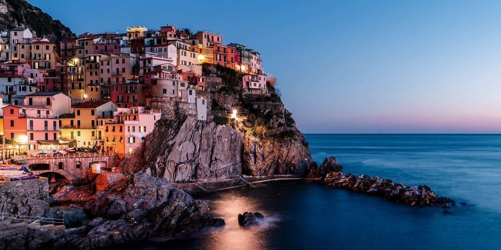 Imagen de los pueblos de Cinque Terre iluminados durante la noche.