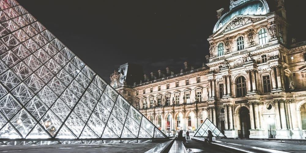 Museo del Louvre iluminado durante la noche en París.
