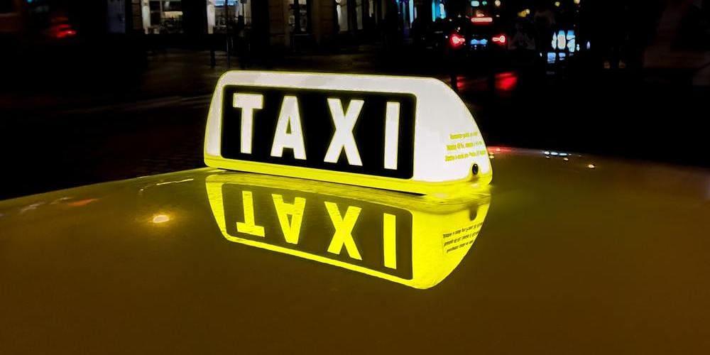 Taxi recogiendo a turistas por la noche en París.