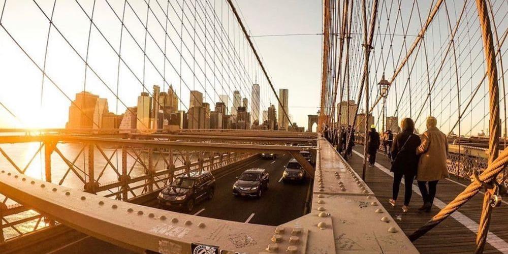 Turistas paseando por el puente de Brooklyn en Nueva York en verano.