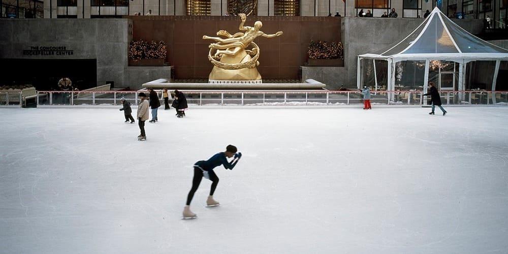 Turistas patinando sobre la pista de hielo bajo el Rockefeller Centre.