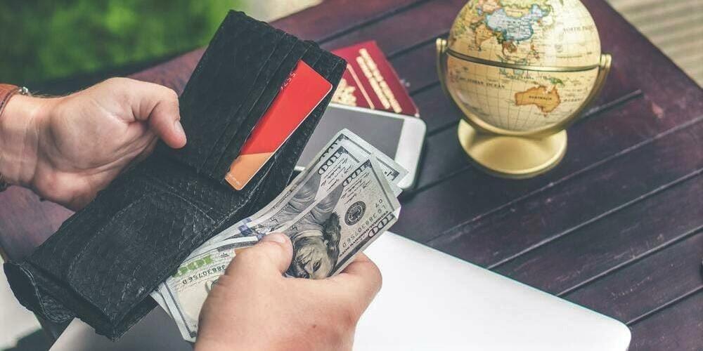 Turista contando los dólares para pagar el transporte en efectivo.