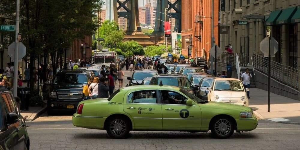 Uno de los taxis verdes de Nueva York frente al puente de Brooklyn.