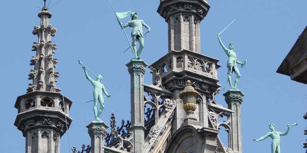 Estatuas en lo alto de las columnas del Museo de la Ciudad de Bruselas.