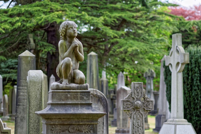 Lápida con una pequeña estatua en un Cementerio de Edimburgo