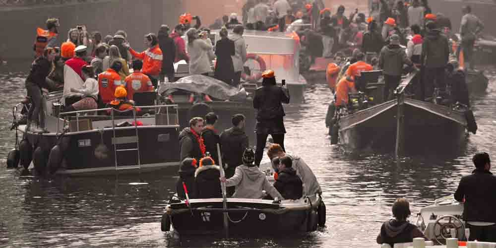 Gente celebrando el King's Day de Ámsterdam en sus canales.