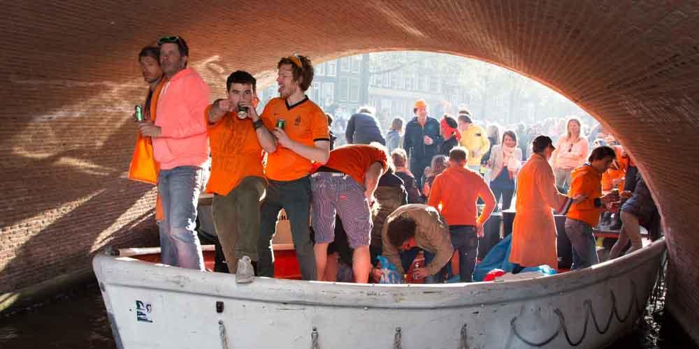Grupo de holandeses celebrando el King's Day de Ámsterdam en una barca.