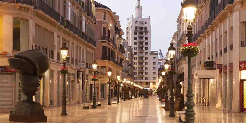 La calle Marqués de Larios iluminada por farolas.