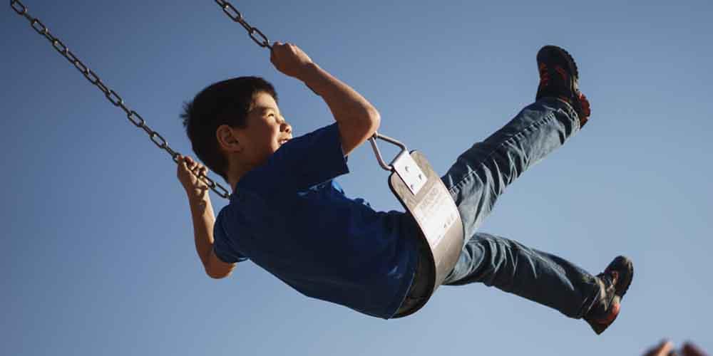 Niño columpiándose en los parques que ver en Salamanca con niños.