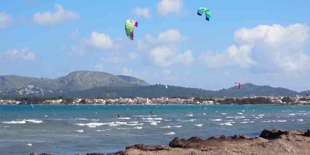 Deportes acuáticos en la playa de Pollensa con los hoteles de fondo.