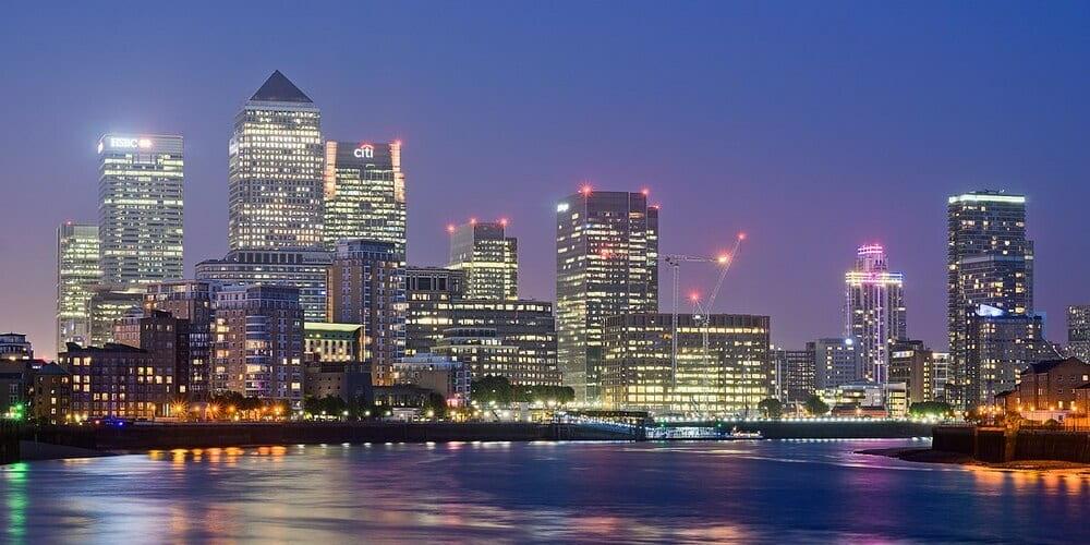 Panorámica de noche de los edificios iluminados de Canary Wharf desde el Támesis
