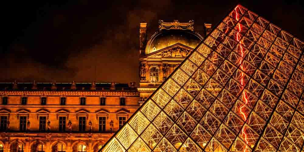En nuestra guía para visitar el Louvre te recomendamos ir de noche para verlo iluminado como en la imagen.