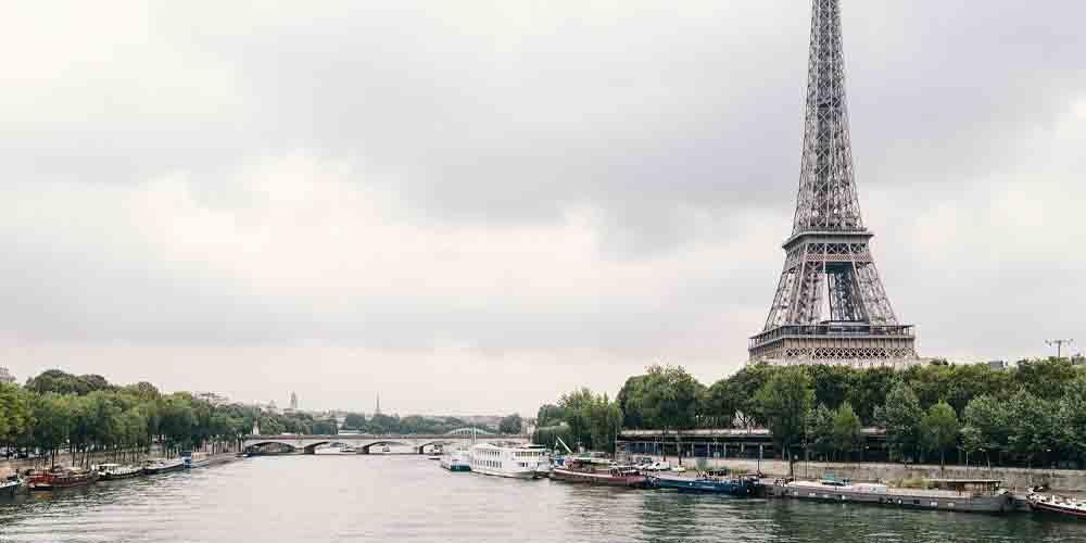 Un barco en frente de la Torre Eiffel navegando en el horario del Bateaux Mouche de París.
